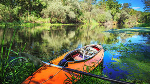 Orange kayak on river with rod on board. Fishing and sport kayak